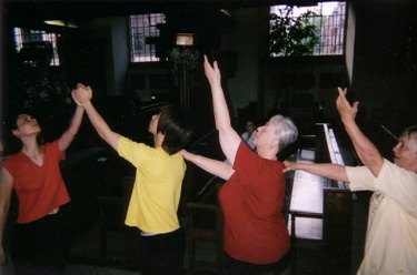 two lines of dancers meet, arms raised