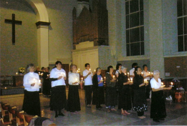 dancers in group, each holding candles